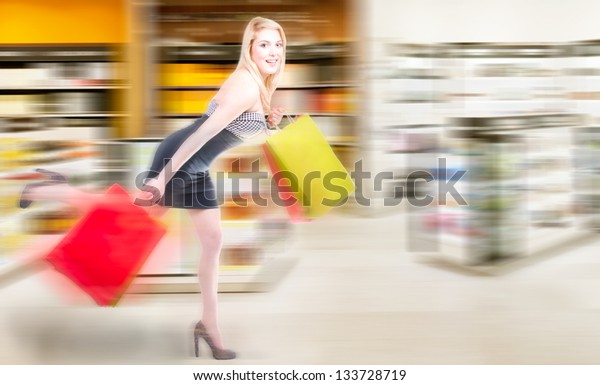 Blonde womanrunning in a shopping spree