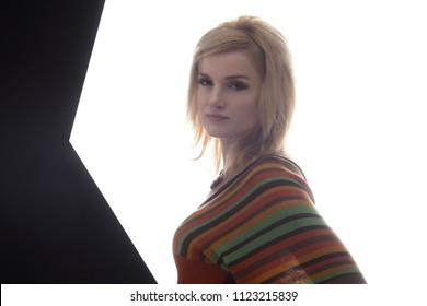 Blonde women in backlight,1960 - 1970 style She is dressed in a knitted blouse in a strip, on her neck she has a beautiful necklace. A clean white background, looks straight into camera