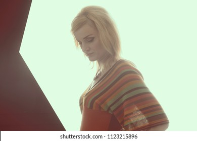 Blonde women in backlight,1960 - 1970 style She is dressed in a knitted blouse in a strip, on her neck she has a beautiful necklace. A clean white background. Isolated image. The girl looks down.