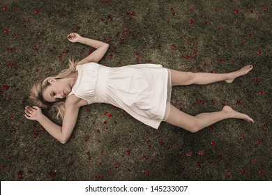 Blonde women wearing white dress laying down with red roses around her