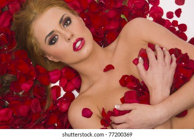 blonde young adult woman pretty laying nude in red rose flower petals