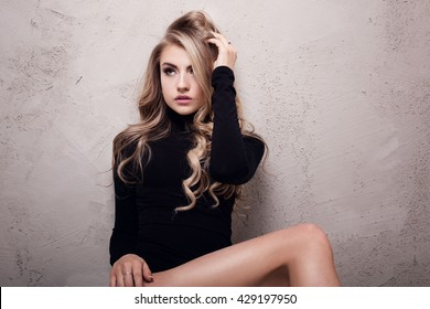 Blonde young beautiful girl posing in studio. Woman with long curly hair.