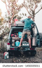 A blonde young caucasian sitting on the car checks and loads his baggage before starting his Australian roadtrip. The car rear door is opened showing all the stuff inside: car bed, camping gear...