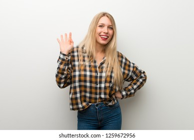 Blonde young girl over white wall saluting with hand with happy expression