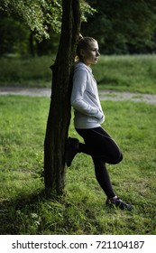 Blonde young woman after work out in the park is waiting for something. Positive emotions.