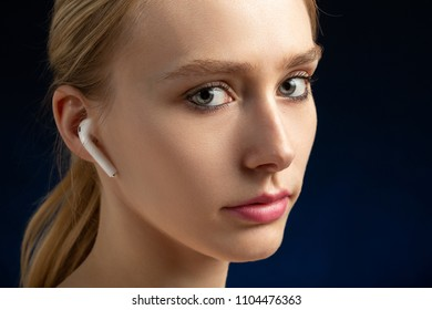 blonde young woman with bluetooth earphones looking at camera