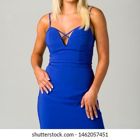 Blonde young woman in a elegant blue dress with hand on hip
