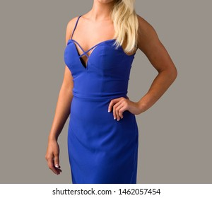 Blonde young woman in elegant blue dress with hand on hip