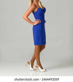 Blonde young woman in elegant blue dress and white high heel shoes with hands on hops