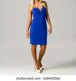 Blonde young woman in elegant blue dress and white high heel shoes