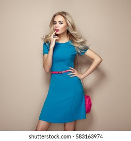 10f93c107 Blonde young woman in elegant blue summer dress. Girl posing on a beige  background.