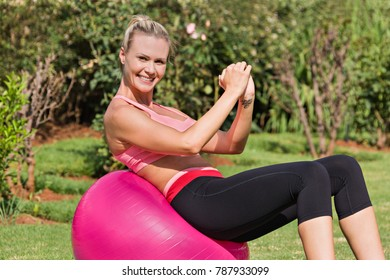 Blonde young woman exercising pilates with the ball at home
