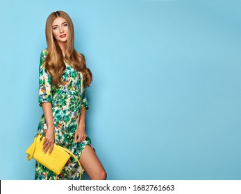 Blonde Young Woman in Floral Spring Summer Dress. Lady in Stylish Summer Outfit. Girl Posing on a Blue Background. Stylish Hairstyle. Spring collection casual clothes