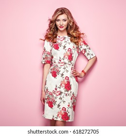 Blonde young woman in floral spring summer dress. Girl posing on a pink background. Summer floral outfit. Stylish wavy hairstyle. Fashion photo. Blonde lady