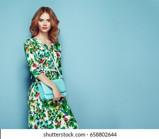 Blonde young woman in floral spring summer dress. Girl posing on a pink background. Summer floral outfit. Stylish wavy hairstyle. Fashion photo. Glamour lady with handbag