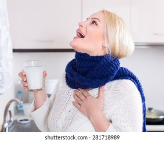 Blonde young woman having pain in throat and doing oral rinsing at kitchen