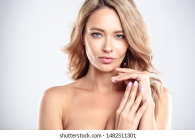 Blonde young woman with healthy curly hair and natural make up . Beautiful model girl with wavy hairstyle. Care and beauty
