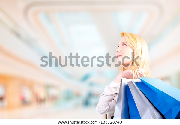 Blonde young woman holding shopping bags looking upwards at copyspace