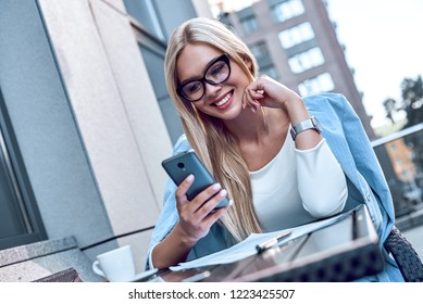 A blonde young woman looks into her smartphone and smiles. She wears glasses and a business suit. Modern technologies and communication