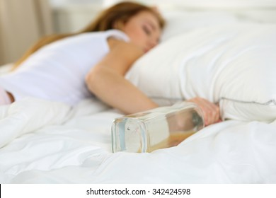 Blonde young woman lying in bed deadly drunken holding near-empty bottle of booze. Female intoxicated with alcohol after tough night party. Alcoholism, habitual drunkenness, pernicious habit concept