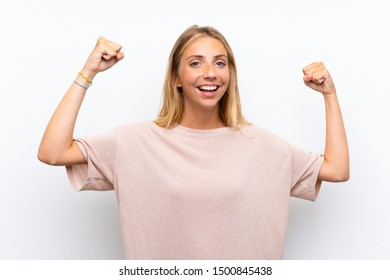 Blonde young woman over isolated white background celebrating a victory