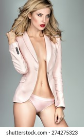 Blonde young woman in pastel lingerie and jacket on gray background