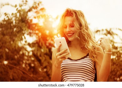 Blonde young woman receiving good news on her cellphone with smile on her face - goldish sunset scene in the park