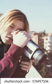 Blonde young woman shooting city from the top roof  with vintage super 8 camera