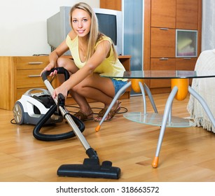 Blonde young  woman in shorts cleaning with vacuum cleaner on parquet floor at home