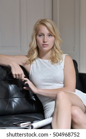 Blonde young woman sitting on the couch looking at view doing nothing.