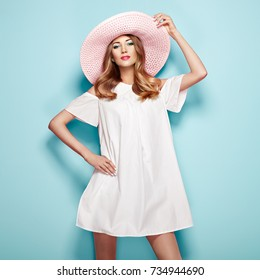 f3d0dc45f702c Blonde Young Woman in Summer White Dress and Summer Hat. Girl Posing on a  Turquoise