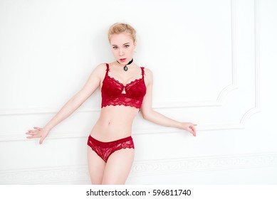 Blonde young woman wearing red lingerie and red chocker, fashion retouched portrait