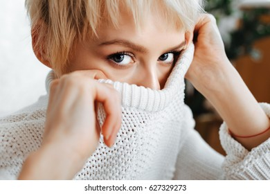 blonde young woman wearing white knitted sweater