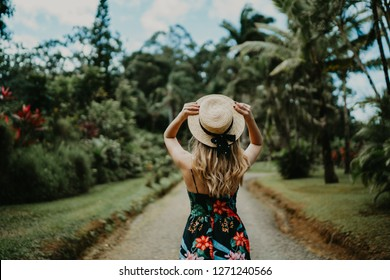 Blonde young women in a Hawaiian floral dress inside the forest wearing a hat with the back at the camera