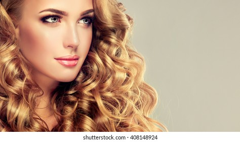 Blondel girl with long wavy hair .  Beautiful  model with curly hairstyle