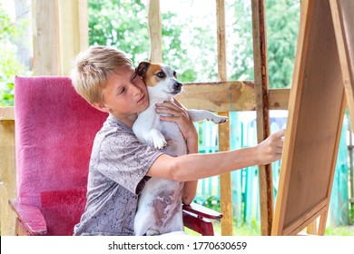 A blond-haired boy sits in a pink chair and holds the dog Jack Russell Terrier in his arms.Caucasian teenager draws on an easel, plener.Painting outdoors, not in studio.Portrait of a child with a dog
