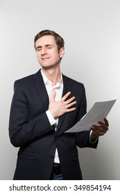 Blond-haired businessman puts his hand on his chest and feels a sigh of relief while in front of a gradient background
