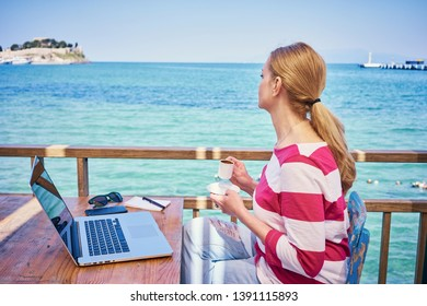 Blondie woman with laptop on the sea. Freelancer business lady working outdoor