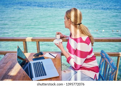 Blondie woman with laptop on the sea. Business lady working outdoor