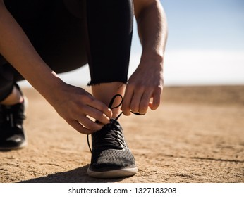 blondie woman wearing sport cloth tying her shoes