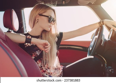 Blondie young girl at the wheel of sport car with red interior with black sunglasses and black leather armlets with metal inserts seating sideward and looking at the road - Shutterstock ID 237381883