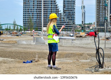 Blondie young girl with yellow helmet and yellow working marker looking on the phone on the construction site - Image