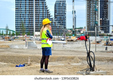 Blondie young girl with yellow helmet and yellow working marker talking on the phone on the construction site - Image