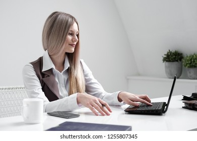 Blondina girl in a business suit sitting at a white table and working on a computer in a white bright office.