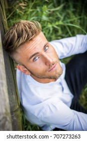 Blondish, blue eyed young man leaning on wood fence in grass lawn at sunset, thinking, looking at camera