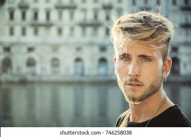 Blondish, blue eyed young man by river at sunset in downtown Turin, Italy, looking at camera