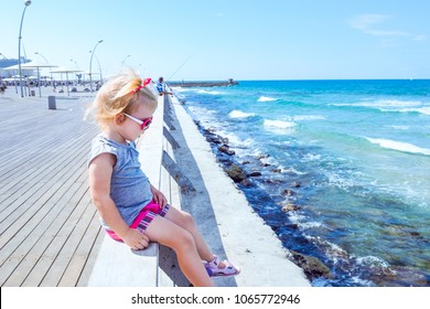 Blondy little baby girl 2-3 year old in pink sunglasses sitting alone on wooden sea railing on the seafront of Tel Aviv. Looking at swash. Childhood concept. Soft selective focus space for text