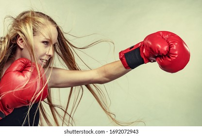 Bloned long hair girl boxer in big fun red gloves playing sports boxing. Female fight for equal rights for women.