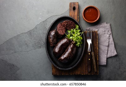 Blood bloody sausages on black cast iron plate with watercress salad. Gray slate background. Traditional chilean bloody sausage - prieta