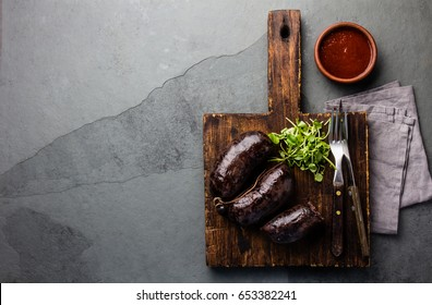 Blood bloody sausages on wooden cutting board with watercress salad and spicy chili sauce. Gray slate background. Traditional chilean bloody sausage - prieta